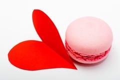 Macarons colorés français avec le coeur de papier rouge sur le backgroun blanc Photographie stock libre de droits