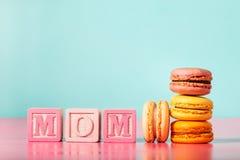 Macarons coloridos com blocos de madeira da mamã no fundo pastel brilhante Foto de Stock Royalty Free
