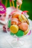 Macarons coloridos em um vidro isolado Fotografia de Stock Royalty Free