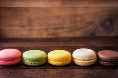 Macarons coloridos en fondo de madera oscuro Imágenes de archivo libres de regalías