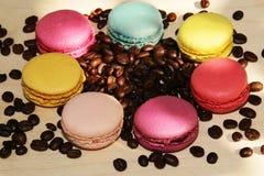 Macarons coloridos franceses tradicionais com os feijões de café no fundo de madeira fotos de stock royalty free