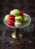 Macarons coloridos franceses tradicionais em um suporte do bolo no fundo escuro com espaço da cópia Bolinhos de amêndoa franceses foto de stock