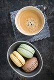 Macarons. Colourful macarons in a small cup with y cup of coffee stock photo