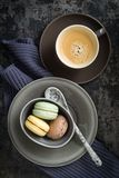 Macarons. Colourful macarons in a small cup with y cup of coffee royalty free stock photos