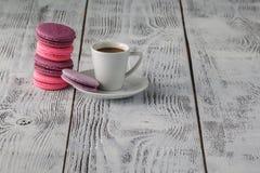 Macarons com a xícara de café no fundo de madeira Fotos de Stock