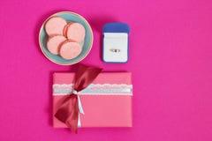 Macarons con el anillo en un fondo rosado Una oferta de la boda, caja que dan el anillo Visión superior, imagen entonada, efecto  Fotos de archivo libres de regalías