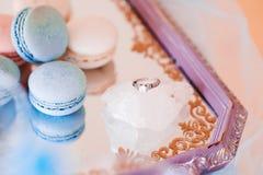 Macarons con la fede nuziale sul pezzo di fine del cristallo sul colpo Fotografia Stock Libera da Diritti
