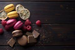 Macarons con los ingredientes sobre una tabla de madera oscura Imágenes de archivo libres de regalías