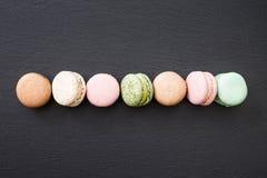 Macarons, configuration d'appartement de vue supérieure, macaron doux sur l'ardoise noire Images stock