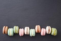 Macarons, configuration d'appartement de vue supérieure, macaron doux sur l'ardoise noire Image libre de droits