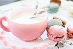 Macarons cor-de-rosa e leite fotografia de stock royalty free