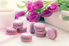 Macarons délicieux doux violets et tulipes fraîches Photographie stock libre de droits