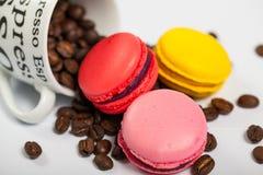 Macarons délicieux français colorés sur les grains de café, tasse avec des grains de café sur la fin blanche de fond  Images stock