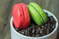 Macarons dans la tasse blanche avec des grains de café photographie stock libre de droits