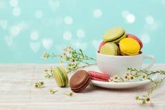 Macarons dans la tasse de café avec des fleurs au-dessus de fond en bon état Images stock