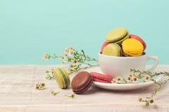 Macarons dans la tasse de café avec des fleurs au-dessus de fond en bon état Image libre de droits