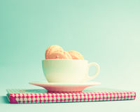 Macarons dans une tasse au-dessus de livre Images stock