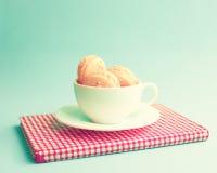 Macarons dans une tasse au-dessus de livre Photo stock