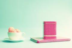Macarons dans une tasse et une boîte de thé Images stock