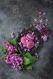 Macarons de Blackberry em flores da placa e do lilás do vintage sobre o cinza Fotografia de Stock