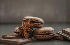Macarons de goût de chocolat ou de café et badiyan français sur le fond foncé Photo stock