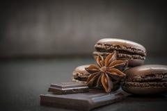 Macarons de goût de chocolat ou de café et badiyan français sur le fond foncé Photographie stock libre de droits