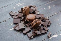 Macarons del chocolate sobre pedazos de chocolate en fondo de madera Cierre para arriba Imagen de archivo
