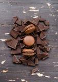 Macarons del chocolate sobre pedazos de chocolate en fondo de madera del vintage Cierre para arriba Imagenes de archivo