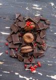 Macarons del chocolate sobre pedazos de chocolate en fondo de madera Visión superior Foto de archivo