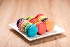 Macarons in der Platte auf hölzerner Tabelle Stockbild