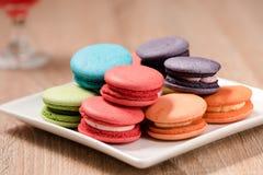 Macarons in der Platte auf hölzerner Tabelle Stockfotos