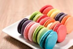 Macarons in der Platte auf hölzerner Tabelle Stockfoto