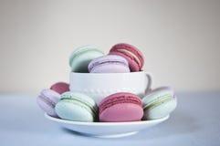 Macarons in der Teetasse und untertasse Stockfotos