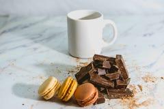 Macarons doces saborosos com a xícara de café no fundo foto de stock