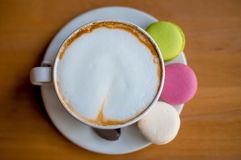 Macarons doces saborosos e copo de caf? Bolinhos de am?ndoa no fundo de madeira Vista superior fotos de stock