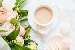 Macarons dolci eleganti del dessert, tazza di caffè e mazzo beige colorato pastello dei fiori su marmo bianco immagine stock