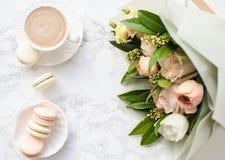 Macarons dolci eleganti del dessert, tazza di caffè e mazzo beige colorato pastello dei fiori su marmo bianco fotografia stock libera da diritti