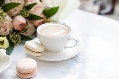 Macarons dolci eleganti del dessert, tazza di caffè e mazzo beige colorato pastello dei fiori su marmo bianco fotografie stock