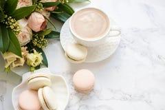 Macarons dolci eleganti del dessert, tazza di caffè e mazzo beige colorato pastello dei fiori su marmo bianco immagini stock libere da diritti