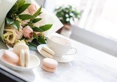 Macarons dolci eleganti del dessert, tazza di caffè e mazzo beige colorato pastello dei fiori su marmo bianco immagine stock libera da diritti