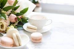 Macarons dolci eleganti del dessert, tazza di caffè e mazzo beige colorato pastello dei fiori su marmo bianco immagini stock
