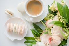 Macarons dolci eleganti del dessert, tazza di caffè e mazzo beige colorato pastello dei fiori immagine stock libera da diritti