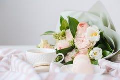 Macarons dolci eleganti del dessert, tazza di caffè e mazzo beige colorato pastello dei fiori fotografia stock libera da diritti