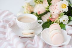 Macarons dolci eleganti del dessert, tazza di caffè e mazzo beige colorato pastello dei fiori fotografie stock libere da diritti