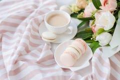 Macarons dolci eleganti del dessert, tazza di caffè e mazzo beige colorato pastello dei fiori immagini stock