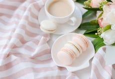 Macarons dolci eleganti del dessert, tazza di caffè e mazzo beige colorato pastello dei fiori immagine stock
