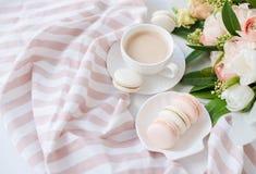 Macarons dolci eleganti del dessert, tazza di caffè e mazzo beige colorato pastello dei fiori fotografie stock