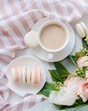 Macarons dolci eleganti del dessert, tazza di caffè e mazzo beige colorato pastello dei fiori immagini stock libere da diritti