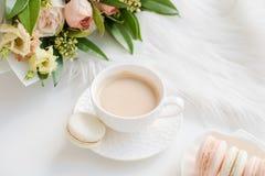 Macarons dolci eleganti del dessert, tazza di caffè e mazzo beige colorato pastello dei fiori fotografia stock