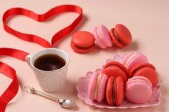 Macarons doux délicieux dans un plat figural sur des macarons de fond, rouges et roses roses images stock